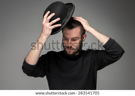 Young man with a mustache and beard raising his hat  in respect and admiration for someone. portrait on gray background. male gaze directed downward
