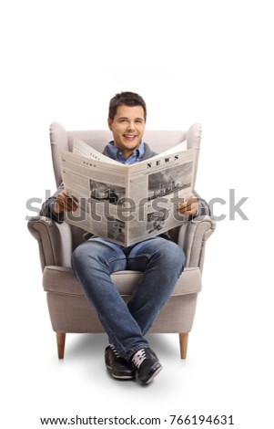 Young man with a newspaper sitting in an armchair isolated on white background