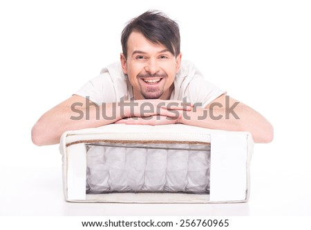 Young man with a nice mattress made of coconut fiber is looking at the camera and smiling. - stock photo