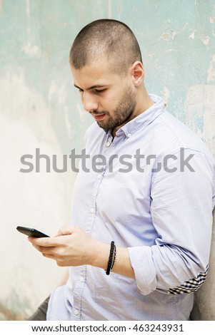 Young man with a phone by the grunge wall