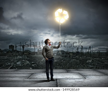 Young man with a recycle symbol against a polluted and ruined landscape