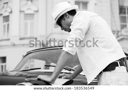 Young man with a road map at the classic car - stock photo