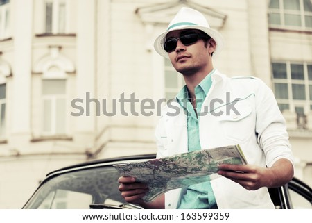 Young man with a road map at the retro car - stock photo