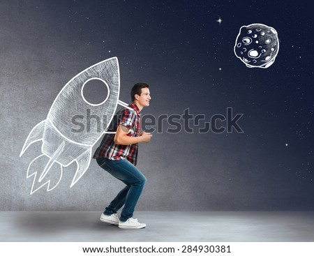 Young man with a rocket on his back - stock photo