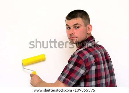 Young man with a roller in her hand is doing repair of room near wall - stock photo