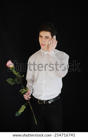 young man with a rose talking on telephone on the black background - stock photo