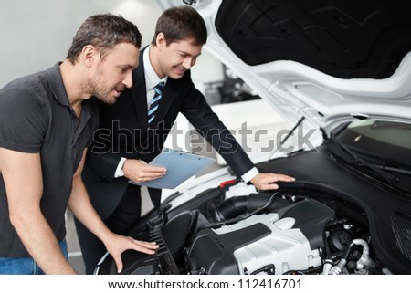 Young man with a salesman in a motor show - stock photo