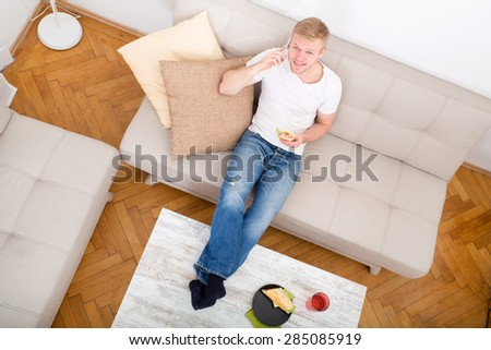Young man with a Sandwich on the Sofa while talking on the phone.  - stock photo