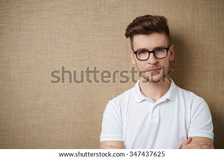 Young man with a serious thoughtful expression and arms folded