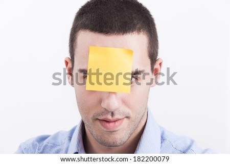 Young man with a sticky note attached to his forehead - stock photo