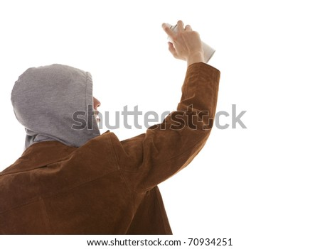 Young man with a tin of spray paint possibly spraying against a wall, isolated on white. - stock photo