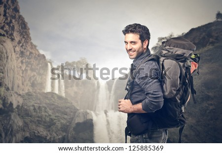 Young man with a travel backpack near a waterfall in Morocco - stock photo