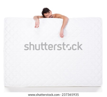 Young man with a white mattress isolated on white background.