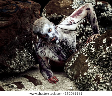young man with a zombie body painting, covered with blood on the beach against a cliff (halloween topic)