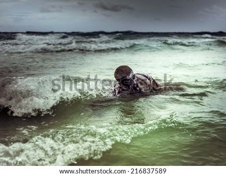 young man with a zombie body painting, covered with blood swimming in the ocean  (halloween topic) - stock photo