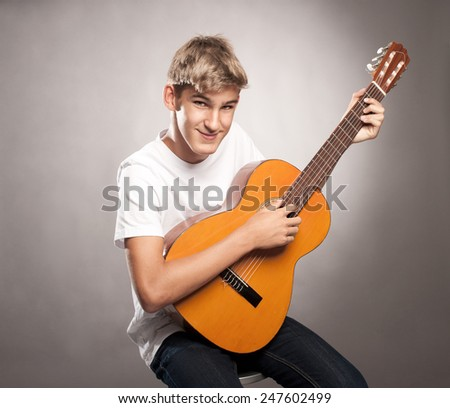 young man with acoustic guitar on a gray background - stock photo