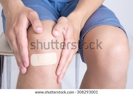 young man with adhesive bandage on his knee - stock photo