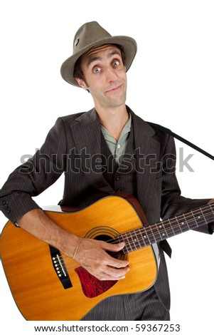 Young man with an accoustic guitar, looking at camera - stock photo