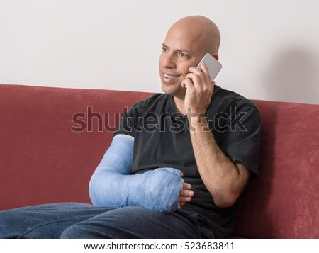 Young man with an arm and elbow in a blue plaster / fiberglass cast at home, happily talking on his phone after having broken his arm