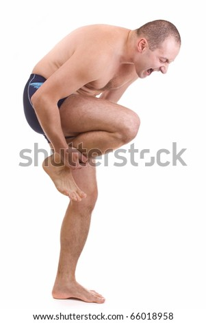 Young man with an expression of severe pain in his leg  . White background.