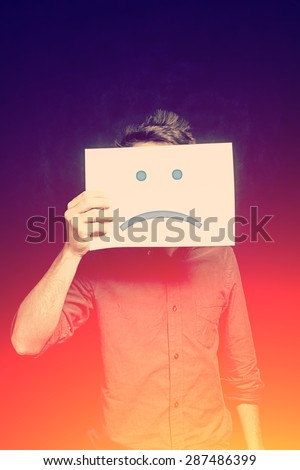 Young man with an unhappy smiley card covering face - stock photo