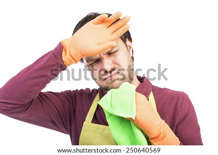 Young man with apron and gloves tired to clean over white background - stock photo