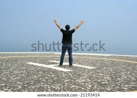 young man with arms open contemplating the ocean in foggy day in the heliport - stock photo
