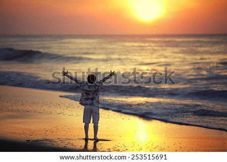 Young man with arms outstretched standing on the beach and looking to the side of sunrise on the ocean - stock photo