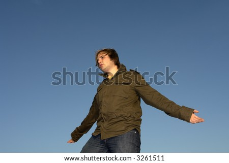 young man with arms wide open at sunset light