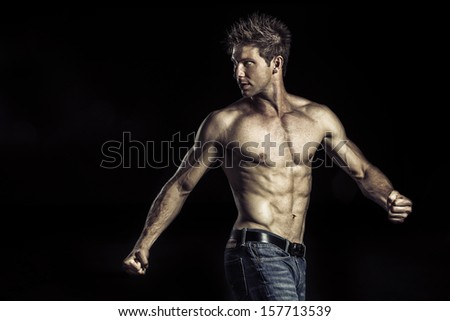 Young man with athletic body turning around and showing his muscles isolated on black background - stock photo