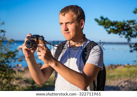 young man with backpack and camera on the beach