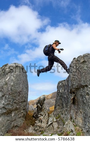 Young man with backpack lands to high rock - low angle, against sky. Shot in Hottentots-Holland Mountains nature reserve, near Grabouw, Western Cape, South Africa. - stock photo
