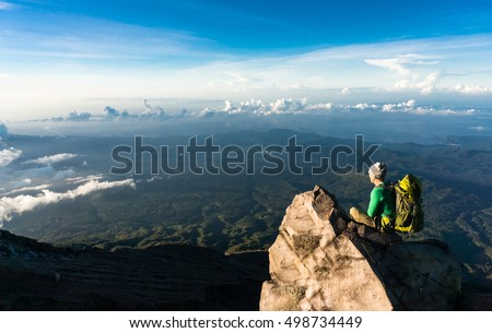 Young man with backpack sitting on a cliffs edge on the top of mountain with gorgeous view to forests, clouds and sea. Volcano Agung, Bali, Indonesia.