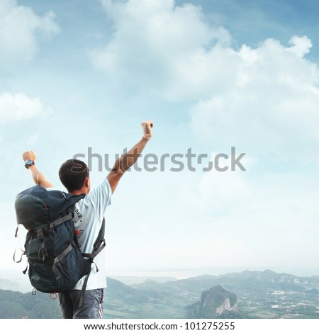 Young man with backpack standing with raised hands on top of a mountain and enjouing valley view - stock photo