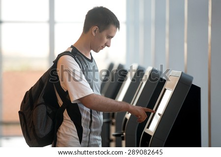 Young man with backpack touching interactive display at self-service transfer machine, doing self-check-in for flight or buying airplane tickets at automatic device in modern airport terminal building - stock photo