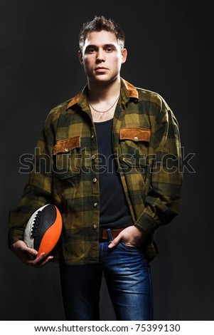 Young man with ball in studio - stock photo