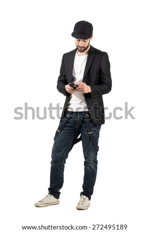 Young man with baseball cap typing on his cellphone. Full body length portrait isolated over white background.  - stock photo