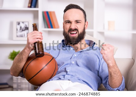 Young man with basketball and beer while watching the game.