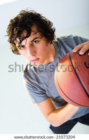 Young man with basketball. He's looking at camera. - stock photo
