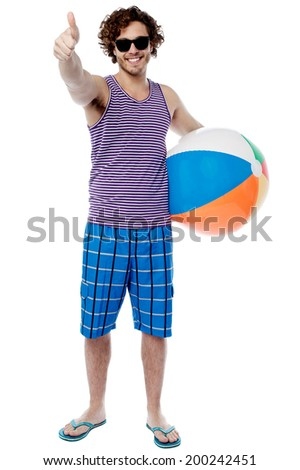 Young man with beach ball and showing thumbs up - stock photo