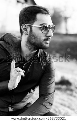 young man with beard and sunglasses posing on the street with a jacket in his hands - stock photo