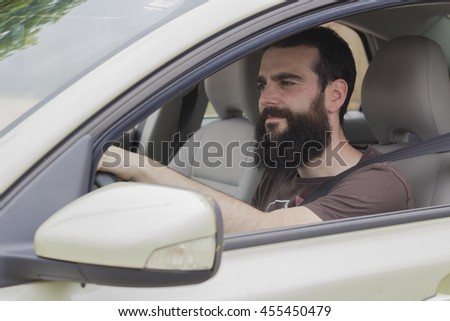 Young man with beard grabbing the steering wheel while driving.