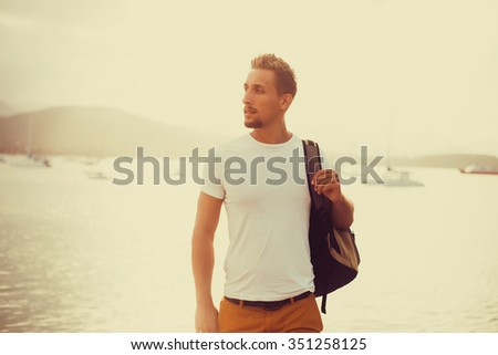 young man with beard posing in a white t-shirt standing on the pier near the sea with a backpack on shoulders - stock photo