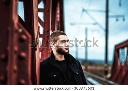 Young man with beard walking on the railway