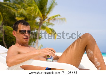 Young man with beer on a tropical beach - stock photo