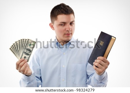 "Young man with Bible looking on the dollar banknotes. ""For where your wealth is, there will your heart be."" Matthew 6:21 - stock photo"