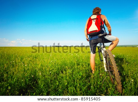 Young man with bicycle standing on green meadow and looking to somewhere
