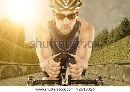 Young man with bike in sunset - stock photo