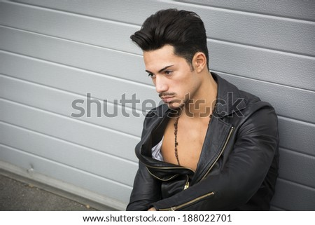Young man with black leather jacket looking away, sitting on the ground outdoors - stock photo