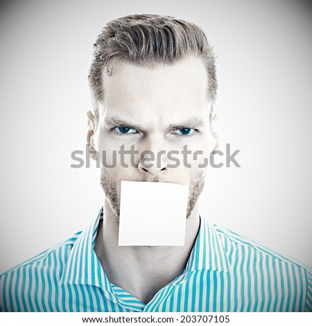 Young man with blank note on his mouth - stock photo